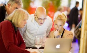 Seo e Backlinks aiutano ad essere trovati in rete. Si vede delle persone con bicchiere di vino davanti un PC a vedere i risultati nei motori di ricerca. Foto: Axel Gross - Grossaufnahmen.