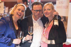Si vede tre persone con una bottiglie di vino e bicchieri nelle mani. Felici d'aver trovato il loro vino preferito grazie alla pubblicità efficace in Wein-Plus.eu