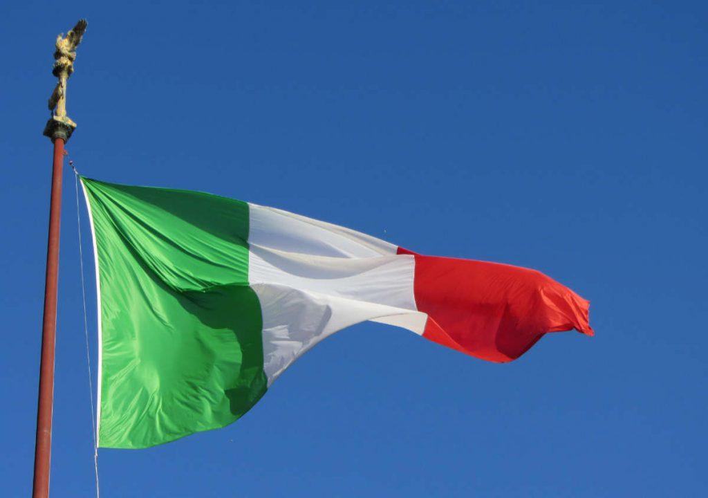 La bandiera italiana nel vento davanti un cielo azzurro. Iluustrazione per le news 20-01 di Wein-Plus Italia