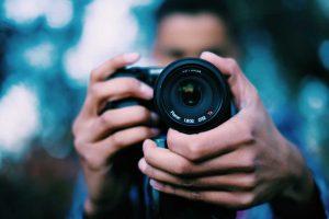 In foto vedi un fotografo la una macchina fotografica. Per soci con la membership in Wein-Plus fotografiamo le bottiglie gratis. Wein-Plus Italia