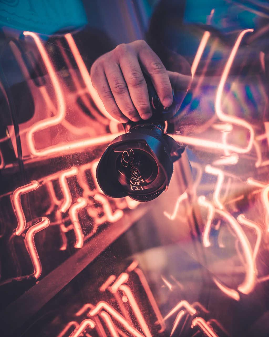 Si vede una macchina fotografica in mano e intorno dei tubi fluorescenti in rosa chiaro. Foto Unsplash per articolo di Wein-Plus Italia