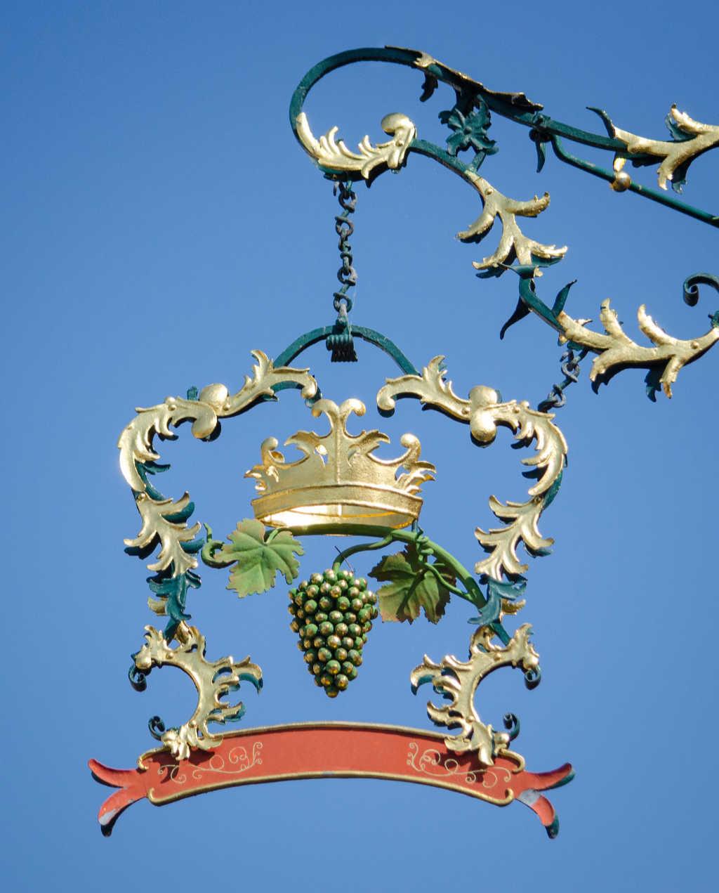 Una insegna di una cantina con corona e grappolo d'uva in oro davanti un cielo blu. Foto Pixabay per articolo Focus Italia 2020 di Wein-Plus