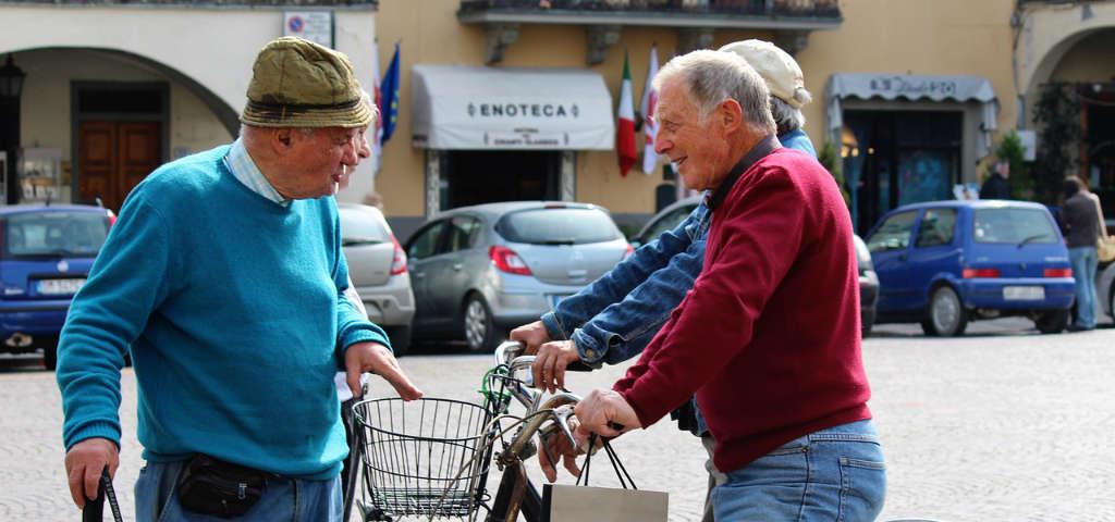 Scena in Toscana di uomini che parlano sulla strada. Magari di buon vino perchè in fondo si vede una enoteca. Foto: Pixabay - Wein-Plus
