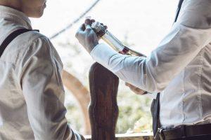 Ottieni più clienti grazie al grande network del vino. In foto due Sommelier che aprono una bottiglia del vino.