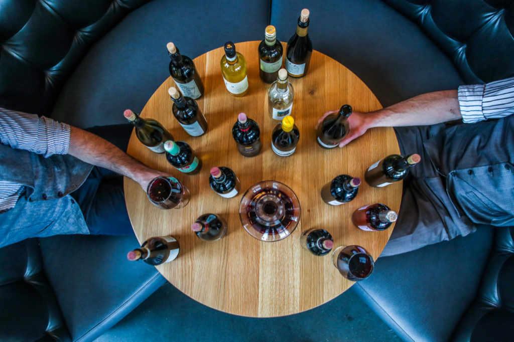 Una serie di bottiglie con due persone che degustano i vini ... magari quelli vini prefertiti dalla redazione wein-plus?