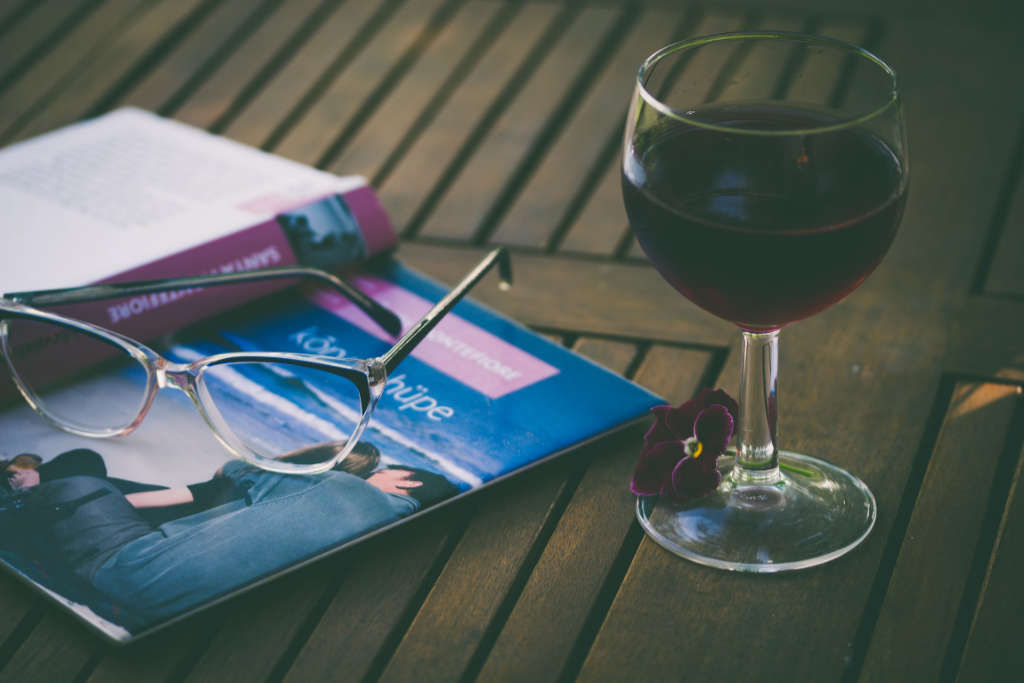 """un bicchiere di vino rosso e un libro per sognare le prossime vacanye dopo il coronavirus. Ilustrazione per l'articolo in Wein-Plus """"i viticoltori in difficoltà """""""